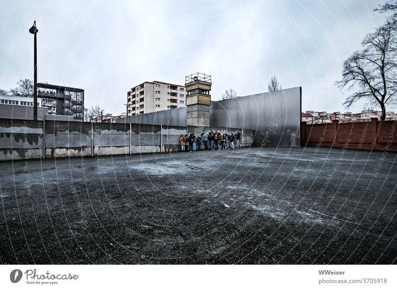 Eine Gruppe junger Touristen auf Tuchfühlung mit der Berliner Mauer Mauerstreifen Gedenkstätte Denkmal Memorial nah Schotter Fläche leerer Vordergrund bewölkt