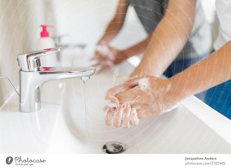 zwei Männer waschen Hände während der Corona Pandemie Händewaschen Hygiene Coronavirus covid-19 Gesundheit Seife Waschbecken Doppelwaschbecken Wasser Wasserhahn