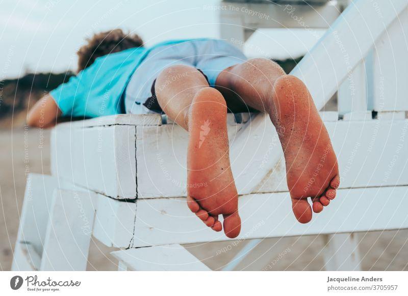 Junge liegt barfuß auf einem Stuhl am Strand Füße Kind Beine Fuß Sommer Barfuß Sand Außenaufnahme Zehen Ferien & Urlaub & Reisen Meer Erholung Mensch Sonne