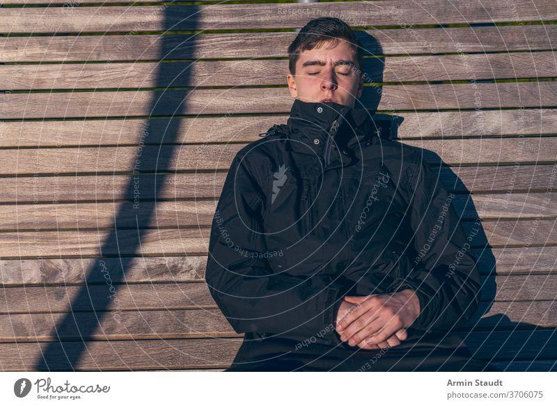 Junger Mann sitzt mit geschlossenen Augen auf einer Bank in der Sonne jung zugeklappt Sitzen Sonnenbad Sonnenlicht im Freien schlafen sich[Akk] entspannen