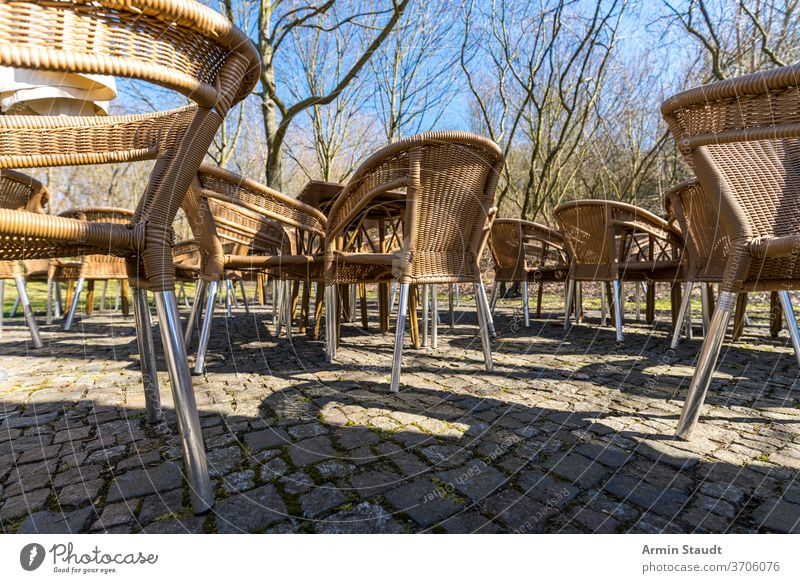 leere Korbstühle eines Cafés auf der Terrasse, draußen Weide Tisch Möbel Restaurant niemand Stuhl im Freien Sitz Straße außerhalb Freizeit Armsessel Rattan