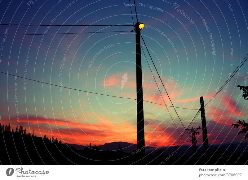 Pfahlmast Silhouette einer leuchtende Straßenlaterne im Dämmerlicht eines schillernden Sonnenuntergangs Himmel Mast Laternenmast Straßenlaternen Lampe