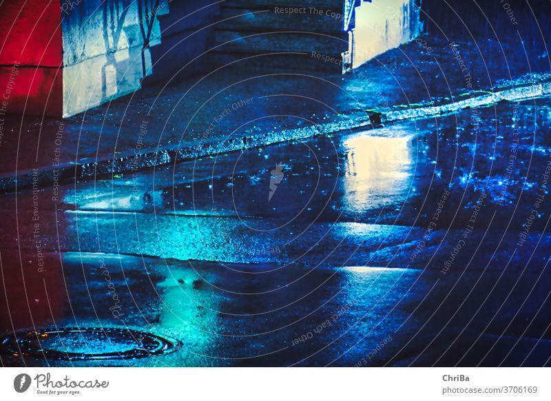 Nächtliche Straße im Regen mit blauer Beleuchtung Gullydeckel Abend Nacht regnerisch Farben Neonlicht Straßenbeleuchtung Citylights urban urbanlove Licht dunkel