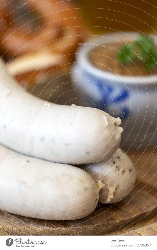 drei bayerische Weißwürste mit Senf Weißwurst Wurst salzig rustikal traditionell Brezel Holztisch Essen Bayern süß Petersilie Mahlzeit Senftopf Oktoberfest