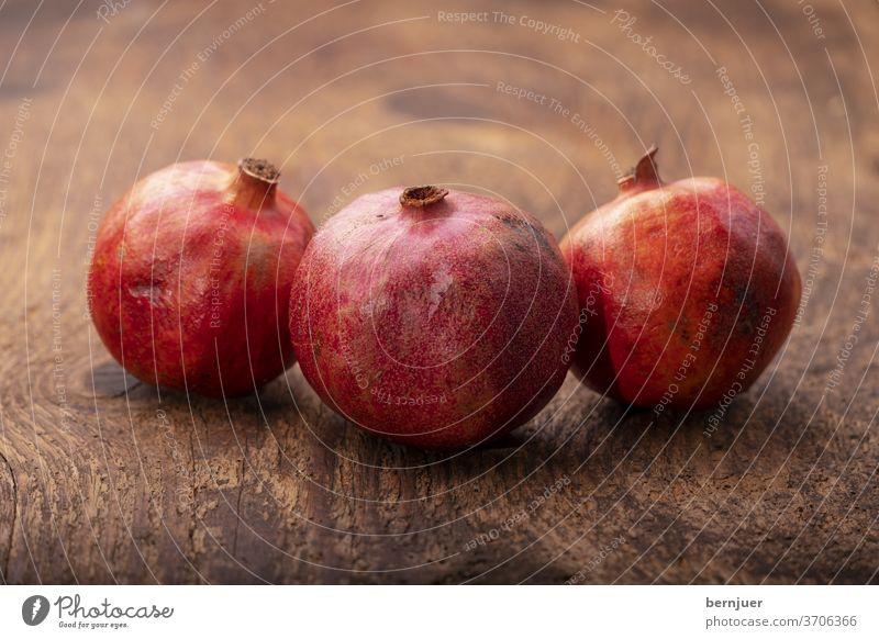 drei Granatäpfel auf dunklem Holz Granatapfel rustikal Hintergrund Obst saftig weiß Essen tropisch exotisch rot süß granatum natürlich Dessert geschnitten