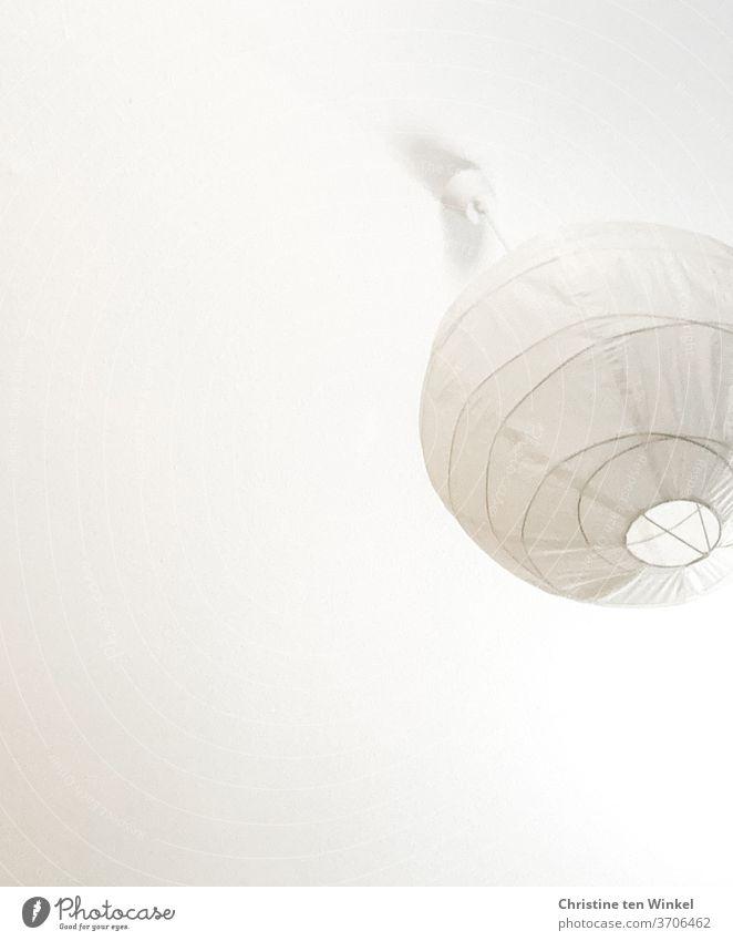 alles weiß... Deckenleuchte aus Papier in Ballonform hängt von einer Zimmerdecke herab. Blick von unten Lampe Papierball Papierlampe Häusliches Leben