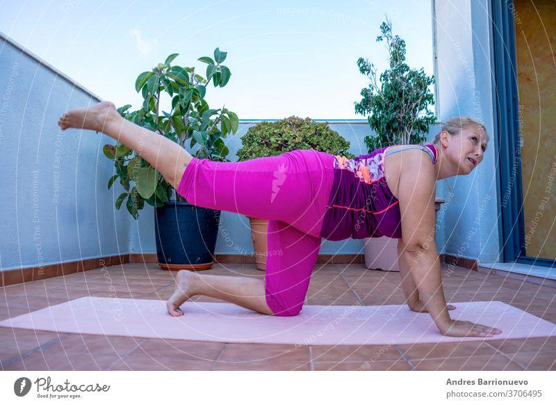 Üben Sie zu Hause. Frau mittleren Alters in schlechter Verfassung, die auf einer Matte auf der Terrasse ihres Hauses trainiert Person Körper aktiv