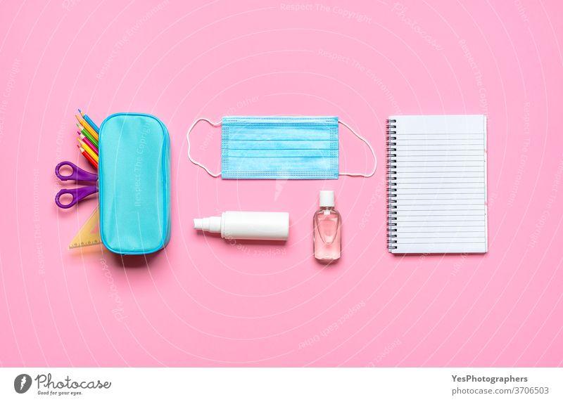 Schulsachen auf einem rosa Schreibtisch. Zurück zu Pandemie-Anforderungen für die Schule Rücken zurück zur Schule Hintergrund blanko blau Konzept Korona COVID