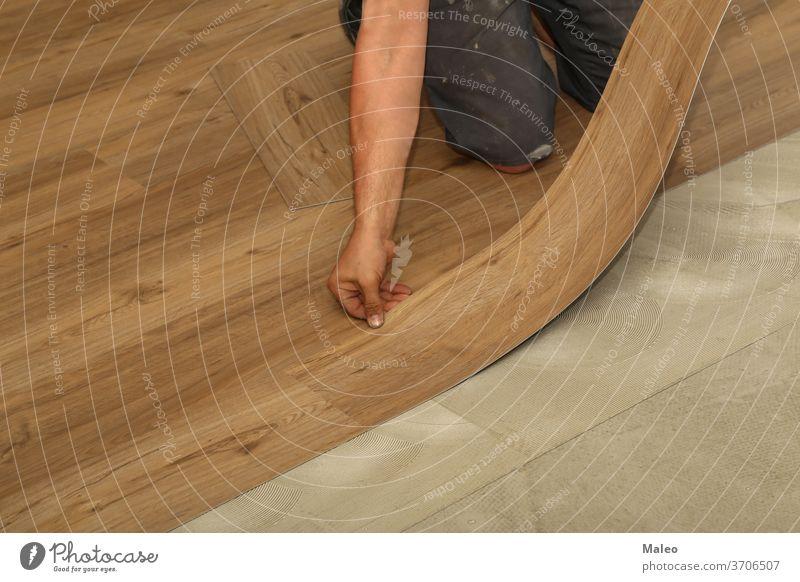 Der Arbeiter beim Verlegen eines neuen Vinylfliesenbodens Installation Fliesen u. Kacheln Stock Hintergrund Bauherr Gebäude Konstruktion Handwerk geschnitten