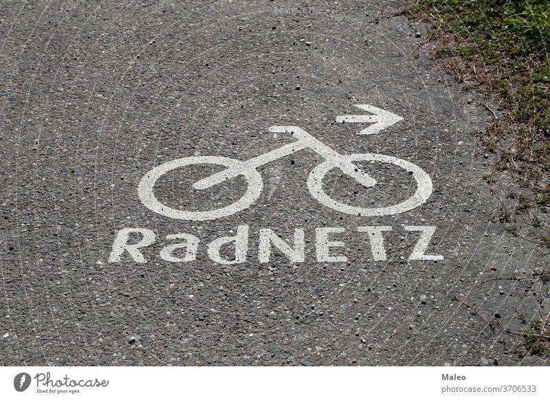 Fahrradwegmarkierungen auf dem Asphalt. Deutscher Text: Fahrrad-Netzwerk Fahrspur Weg Straße Zeichen Symbol urban Hintergrund Großstadt Regie Bahn Verkehr weiß