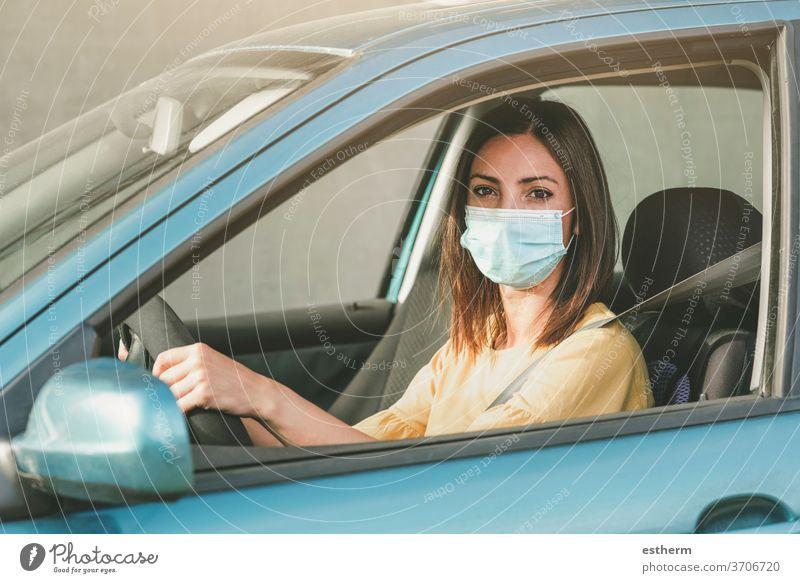 Junge Frau fährt Auto mit medizinischer Maske im Gesicht Coronavirus Virus covid-19 medizinische Maske PKW Laufwerk Sicherheit Ausflug reisen Ausflugsziel