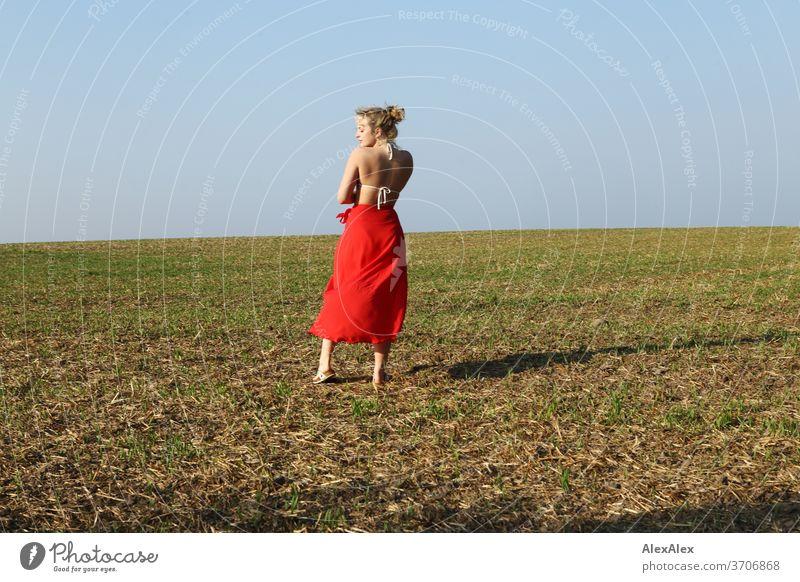 Portrait in Hinteransicht einer jungen Frau mit Bikini- Top und rotem Rock auf einem Feld Licht sportlich feminin Gefühle emotional Porträt Zentralperspektive