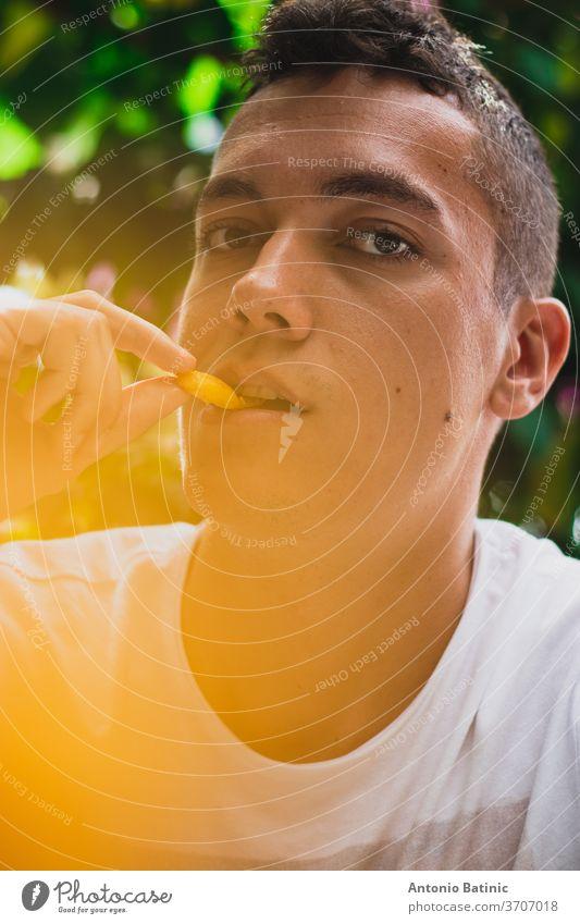 Nahaufnahme eines erwachsenen, gut aussehenden Mannes beim Verzehr von Pommes Frites, gelbes Glühen Bokeh durch die Kartoffeln heiß Fröhlichkeit Farbe gebraten