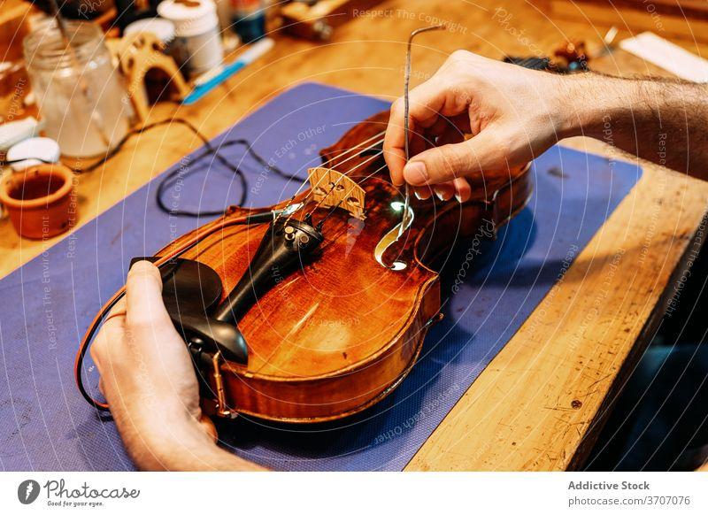 Anonymer Geigenbauer beim Einbau des Stimmstocks in die Geige Zupfinstrumentenmacher Klang einstecken installieren machen Instrument Kunstgewerbler Handwerk