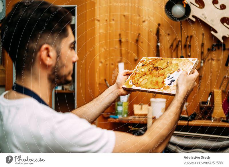 Geigenbauer bei der Arbeit mit Lack in der Werkstatt Zupfinstrumentenmacher lackieren vorbereiten Reparatur Kunstgewerbler mischen Firnis wiederherstellen Mann