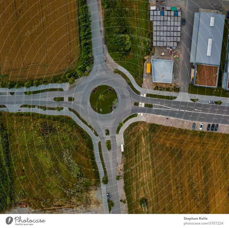 Luftaufnahme eines Verkehrskreisels an einer Hauptstraße in Deutschland von oben nach unten. Kreisverkehr hoch Straße Hintergrund Antenne Weg Sommer Transport