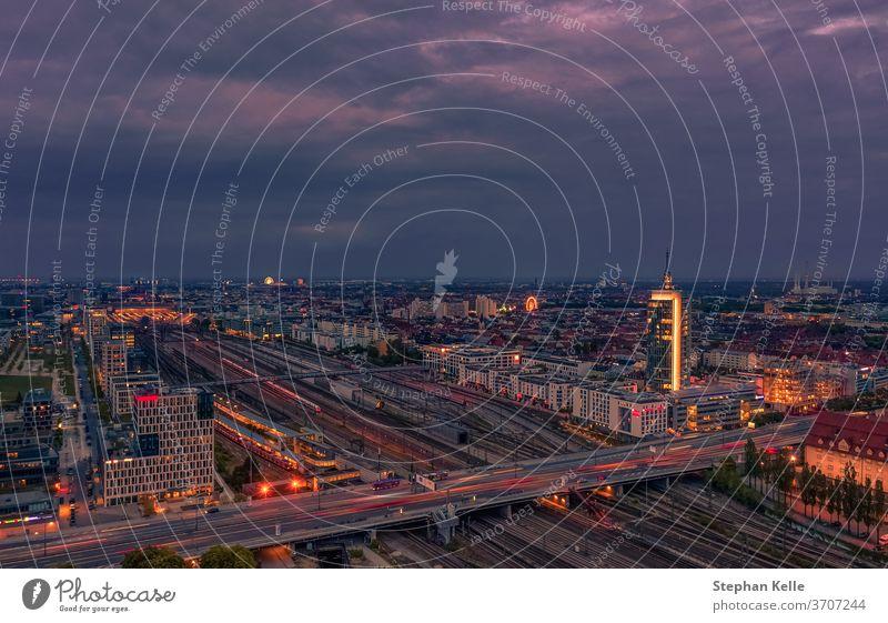 Blick über München zur Hauptverkehrszeit an der Donnersberger Brücke mit den Lichtern der Autos im Hochwinkel. Deutsch Ansicht Büro Turm violett Himmel Straße