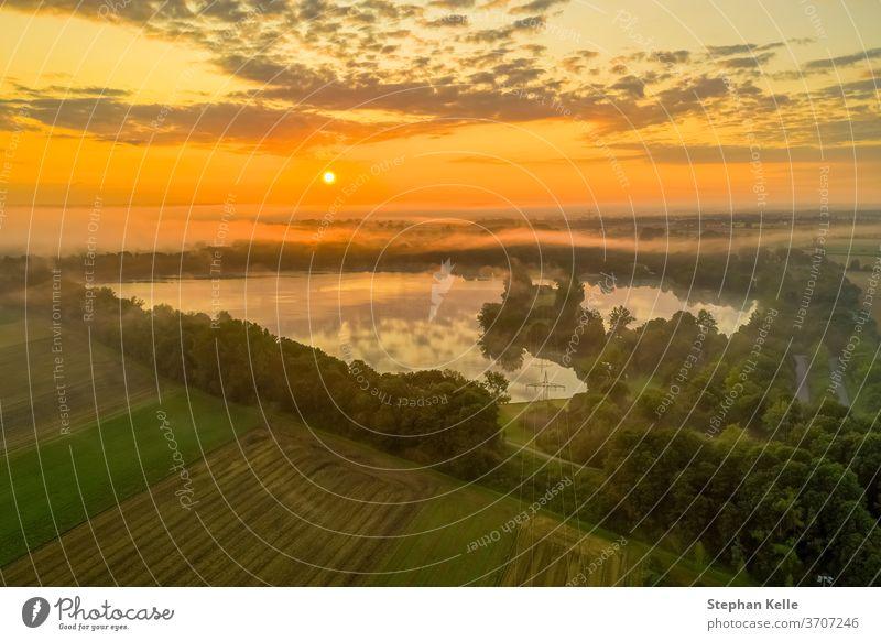 Deutschland, ein kraftvoller Sonnenaufgang über einem nebligen See, Moment purer Natur. Morgen Feld Himmel Hintergrund Sommer glühen Nebel Baum Wasser orange