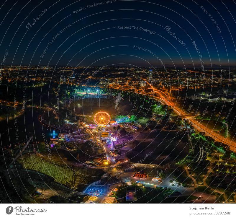 ein eindrucksvolles Nachtansichtsfoto über München vom Olympiaturm beim nächtlichen ImPark-Fest mit beleuchtetem Riesenrad. Spaß Verkehr mit langer Exposition