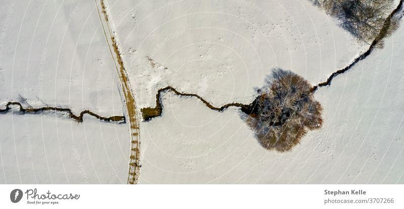 Winterlandschaft: Ein einsamer Baum, der von einem kleinen Bach durchquert wird, Landschaft voller Schnee. Fluss Single Straße allein Textfreiraum Dröhnen
