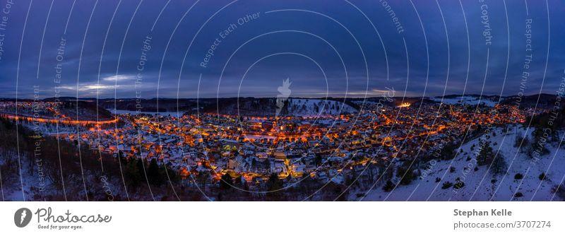 Verschneite Stadtlandschaft der baden-wuerttembergischen Stadt Albstadt in Deutschland zur spaeten Abendstunde mit gluehenden Lichtern. albstadt Winter Schnee