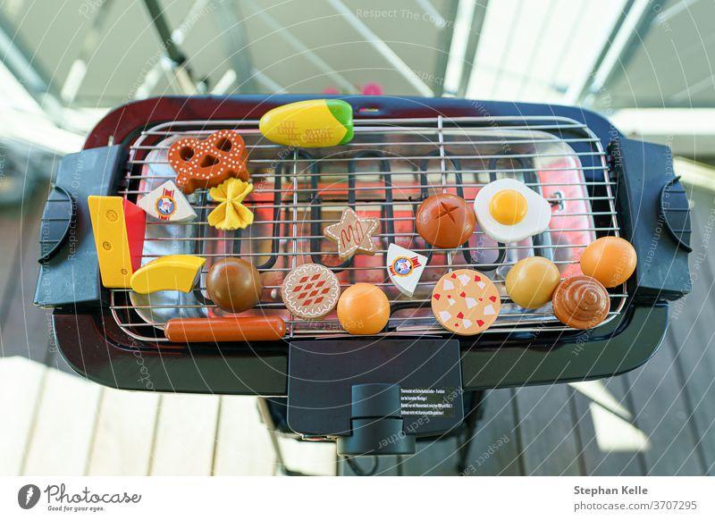 Ein elektronischer Grill auf dem Balkon voll reserviert mit Spielzeuggemüse und Würstchen Grillrost Lebensmittel heimwärts Braten Sommer Rippen grillen