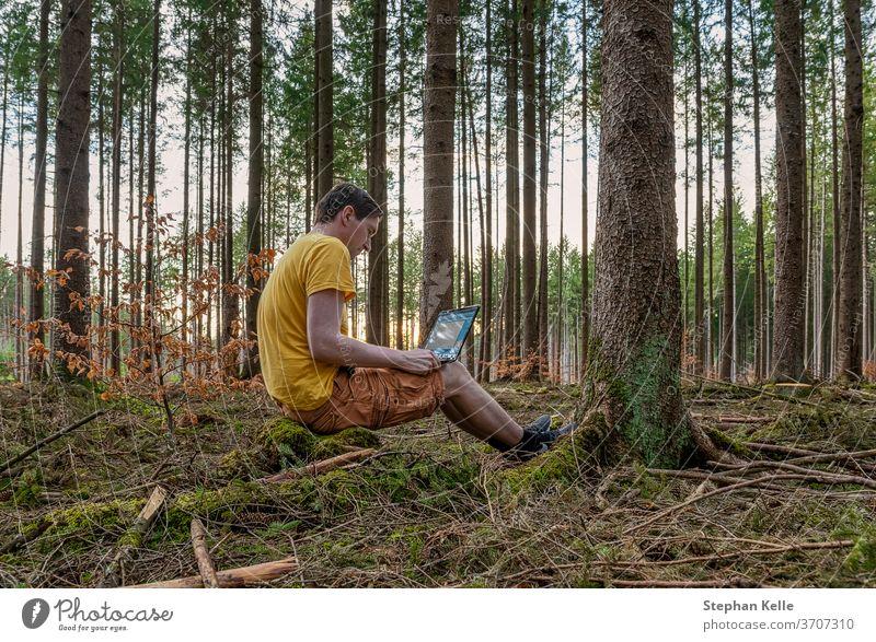 Ein Mann, der mit seinem Laptop in einem Wald an der frischen Luft arbeitet und auf einem Baumstamm sitzt. arbeiten gemütlich Gesundheit Computer Beton grün