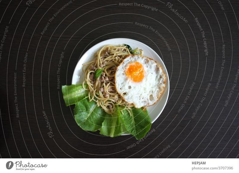 Spaghetti mit Thai-Basilikum-Gewürzsoße mit Spiegelei , Fusion nach thailändischer Art Asien asiatisch Hintergrund Nahaufnahme Essen zubereiten Küche lecker
