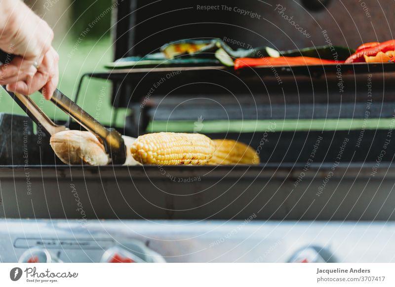 eine Person steht am Grill mit Grillzange und Gemüse Mann Frau grillen Mais Brot Zucchini Lebensmittel Fleisch Grillrost Ernährung Grillsaison lecker Abendessen