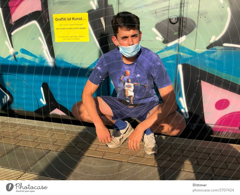 Junger Mann mag Graffiti hat jedoch Insuffizienzen beim Maskentragen Jugendlicher Schutzmaske Bahnsteig Russenhocke Mund-Nasen-Schutz