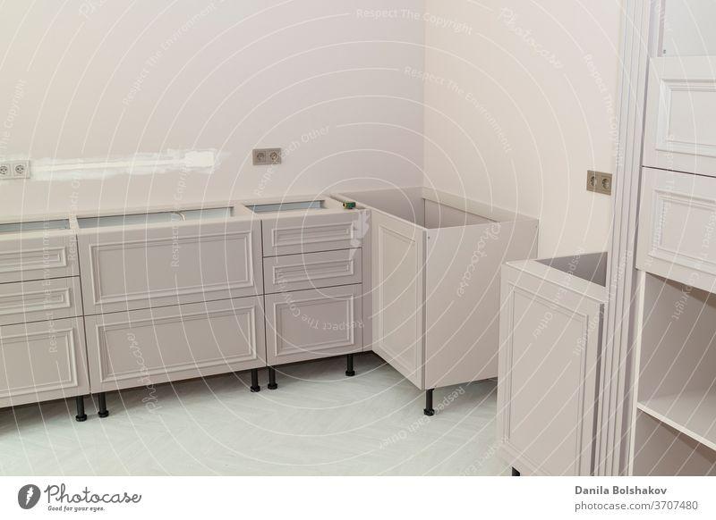 Ansicht der neuen unteren Küchenschubladen mit Türen in der Installationsphase und Steckdosen an der Wand bauen Erhaltung Golfloch Hartholz Stil Gerät