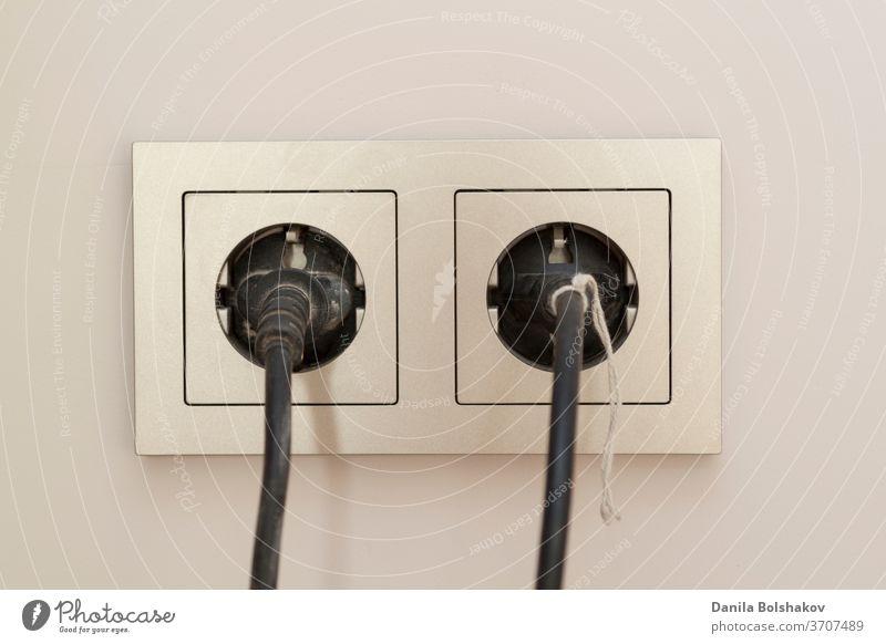 zwei schwarze Stecker werden in eine Doppelsteckdose mit Rahmen eingesteckt technisch Elektronik Verlängerungskabel Stromversorgung zweipoliger Stecker