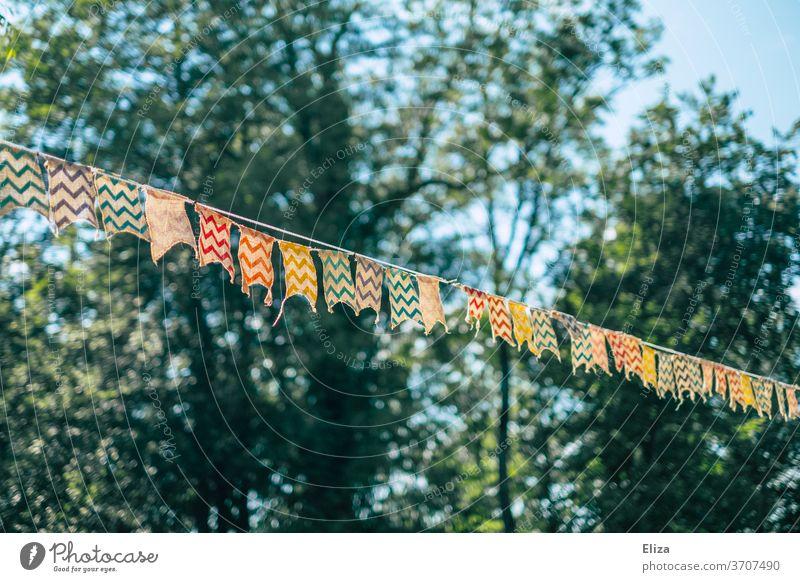Eine bunte Wimpelkette zwischen Bäumen bei einer Gartenparty Party bung geschmückt Dekoration Geburtstag Kindergeburtstag Girlande Dekoration & Verzierung