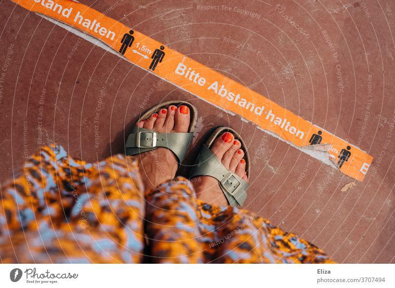 Eine Frau steht vor einer Abstandsmarkierung zum Abstand halten in Zeiten von Corona Markierung Einzelhandel Gastronomie Boden fußboden Sommer Füße Hinweis