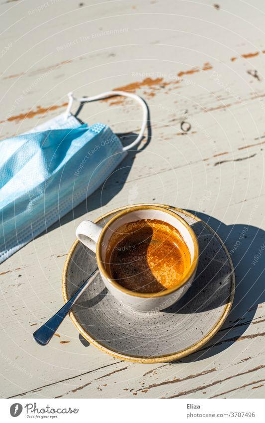Espresso trinken im Café mit Mundschutz weil Corona ist Gastronomie Kaffee Tasse Maske Kaffeepause genießen Maskenpflicht Heißgetränk Tisch Sonne Kaffeetrinken