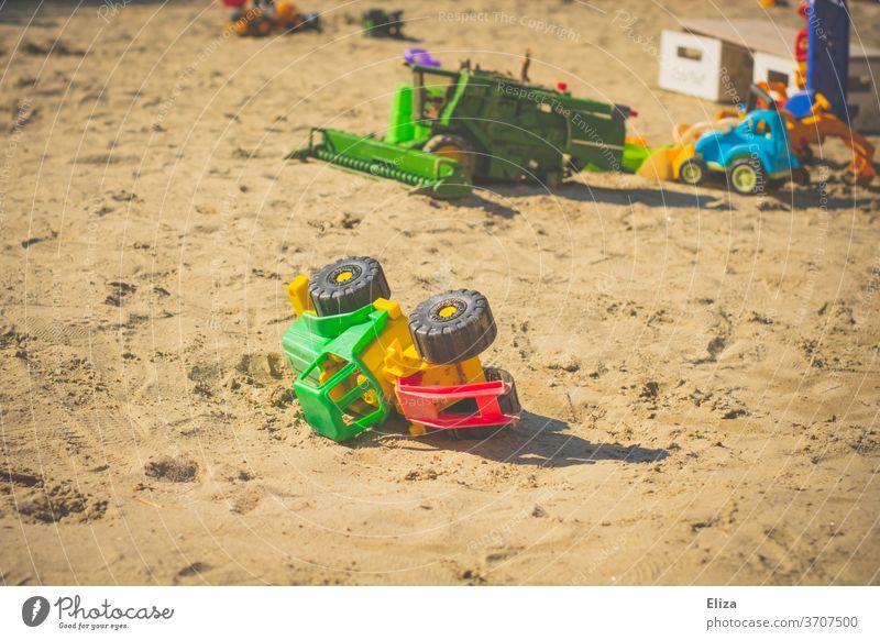 Spielzeug Traktor im Sandkasten. Draußen spielen mit Sandspielzeug. Spielzeugtraktor Spielen Kindheit Kindergarten Spielplatz Sommer Kinderspiel draußen bunt