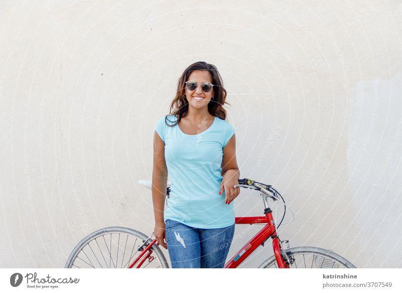 Junge Frauen mit Fahrrad bleiben in der Nähe einer Mauer jung Mädchen anhaben Attrappe T-Shirt Jeanshose Aufenthalt Wand Lächeln Rundhals Bekleidungsmockup
