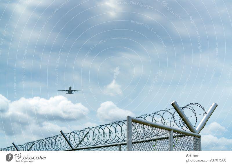 Flugzeug fliegt auf blauem Himmel und weißen Wolken über einem Metallzaun. Luftfahrt-Geschäft. Verkehrsflugzeug. Luftverkehr. Zaun für Sicherheit und Schutz. Luftfahrt-Geschäft. Reisen mit dem Flugzeug.
