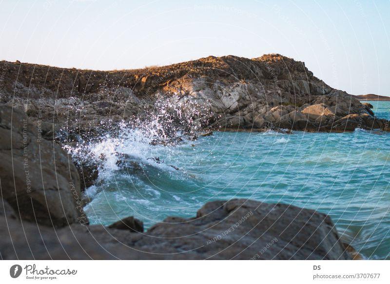 Berge im Meer bei Sonnenuntergang malerisch Ufer Meereslandschaft winken Schönheit Ansicht im Freien Insel Tourismus Hintergrund Stein Strand Küstenlinie Himmel