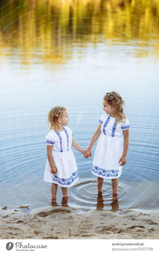Zwei bezaubernde kleine Schwestern, die an einem warmen und sonnigen Sommertag lachen und sich umarmen. zwei Schwestern in weißen Kleidern in der Nähe des Wassers.