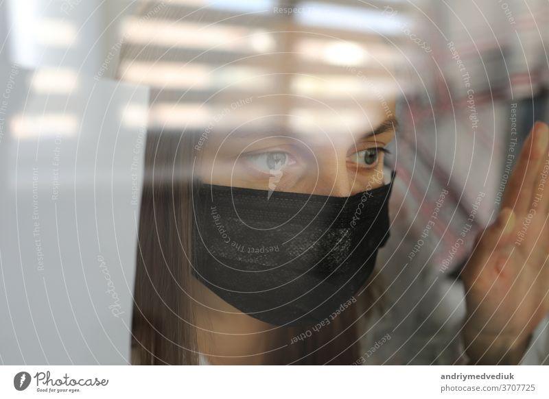 junge frau in einer medizinischen maske hinter einer fensterglasscheibe zu hause. konzept der quarantäne der coronavirus-pandemie, covid 19. selektiver fokus