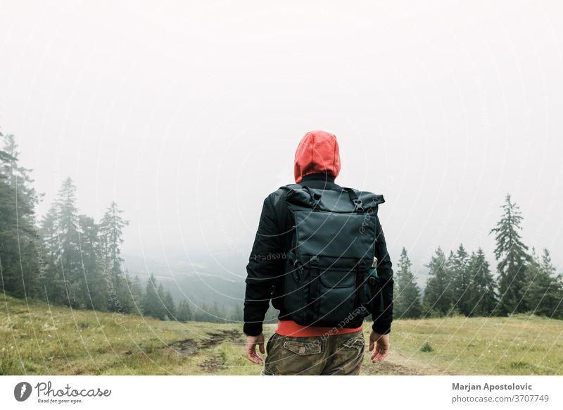 Naturforscher genießt den Blick auf eine neblige Bergkette Abenteuer allein Rucksack Backpacker Umwelt erkunden Entdecker erkundend Nebel Wald Freiheit grün