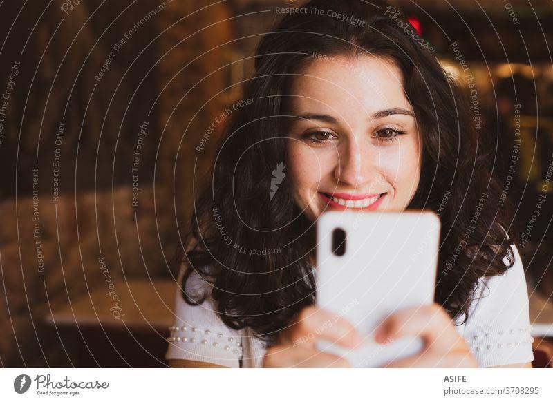 Glückliche junge schöne Frau benutzt ihr Smartphone in einer Bar Mädchen Café Porträt Lächeln Person Freude Menschen zahnfarben Gesicht abschließen Handy