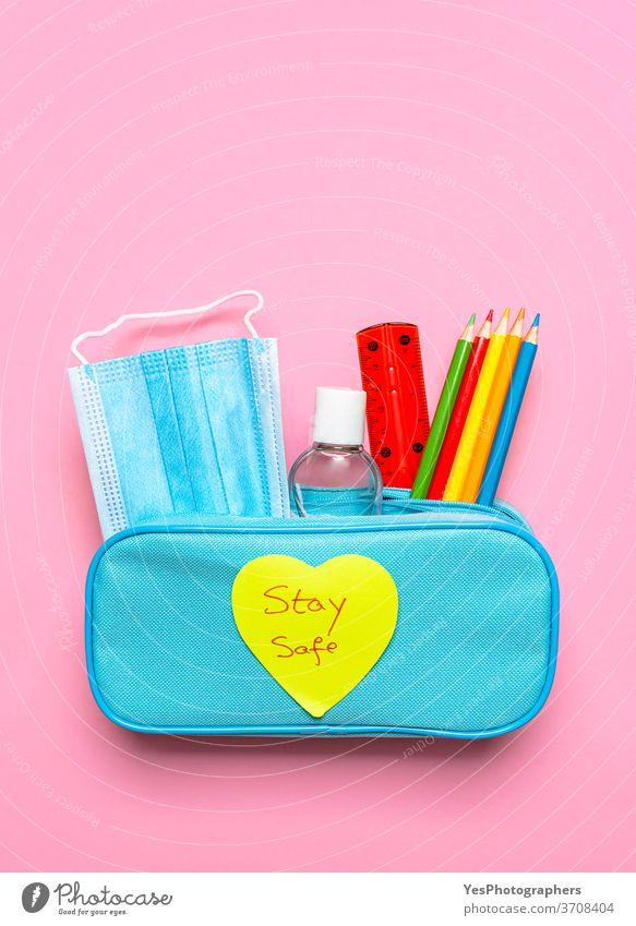 """Federmäppchen mit Gesichtsmaske, Desinfektionsmittel und Buntstiften. Schulsachen mit """"stay safe""""-Botschaft Rücken zurück zur Schule Hintergrund blau Pflege"""