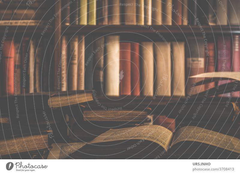 viele alte Bücher liegen aufgeschlagen und gestapelt vor einem Bücherregal in der Bibliothek - das geballte Wissen Buch Literatur Bildung bilden lernen