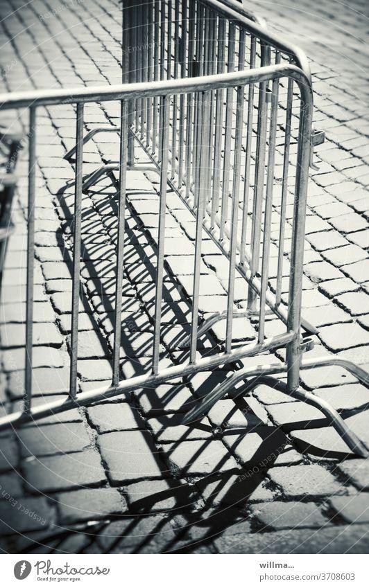 Absperrgitter Absperrung Metall Gitter Schutz Sicherheit Barriere Corona Einschränkung Pflastersteine sw Metallgitter Metallzaun Bauzaun Baustelle Menschenleer