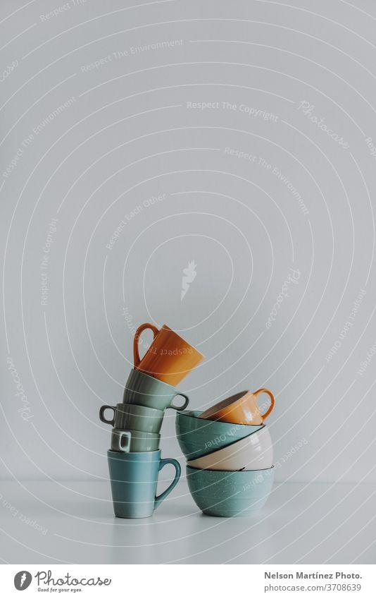 Minimalistische und abstrakte Komposition mit Tassen und tiefen Tellern. Sie stehen auf weißem Hintergrund. Textfreiraum Denken gerade Platten Becher Idee