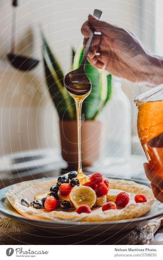 Köstlicher Crêpe mit Bananen, Heidelbeeren, Himbeeren und Honig. Die Küche ist mit einem schönen natürlichen Licht beleuchtet. Wir können sehen, wie der Honig vom Löffel fällt.