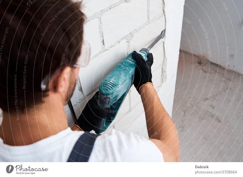 Mann mit Abbruchhammer entfernt Stuck von der Wand. Konzept der Renovierung Abriss Hammer bohren Hand Konstruktion Gerät Arbeit Werkzeug Industrie Maschine