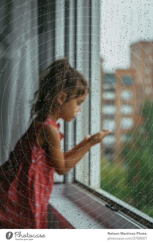Kleines Mädchen, das an einem regnerischen Tag durch das Fenster in ihrem Schlafzimmer schaut. Sie steht auf einem weißen Stuhl, rückwärts gewandt. Wir können Tropfen im Kristall sehen.